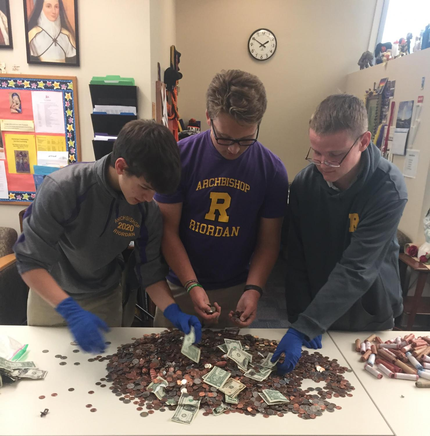 Michael Gray '20, Zachary Phillips '20, and Caelan Bevan-Abel '19 count coins and cash donated to the Billy Choy AIDS Penny Drive.