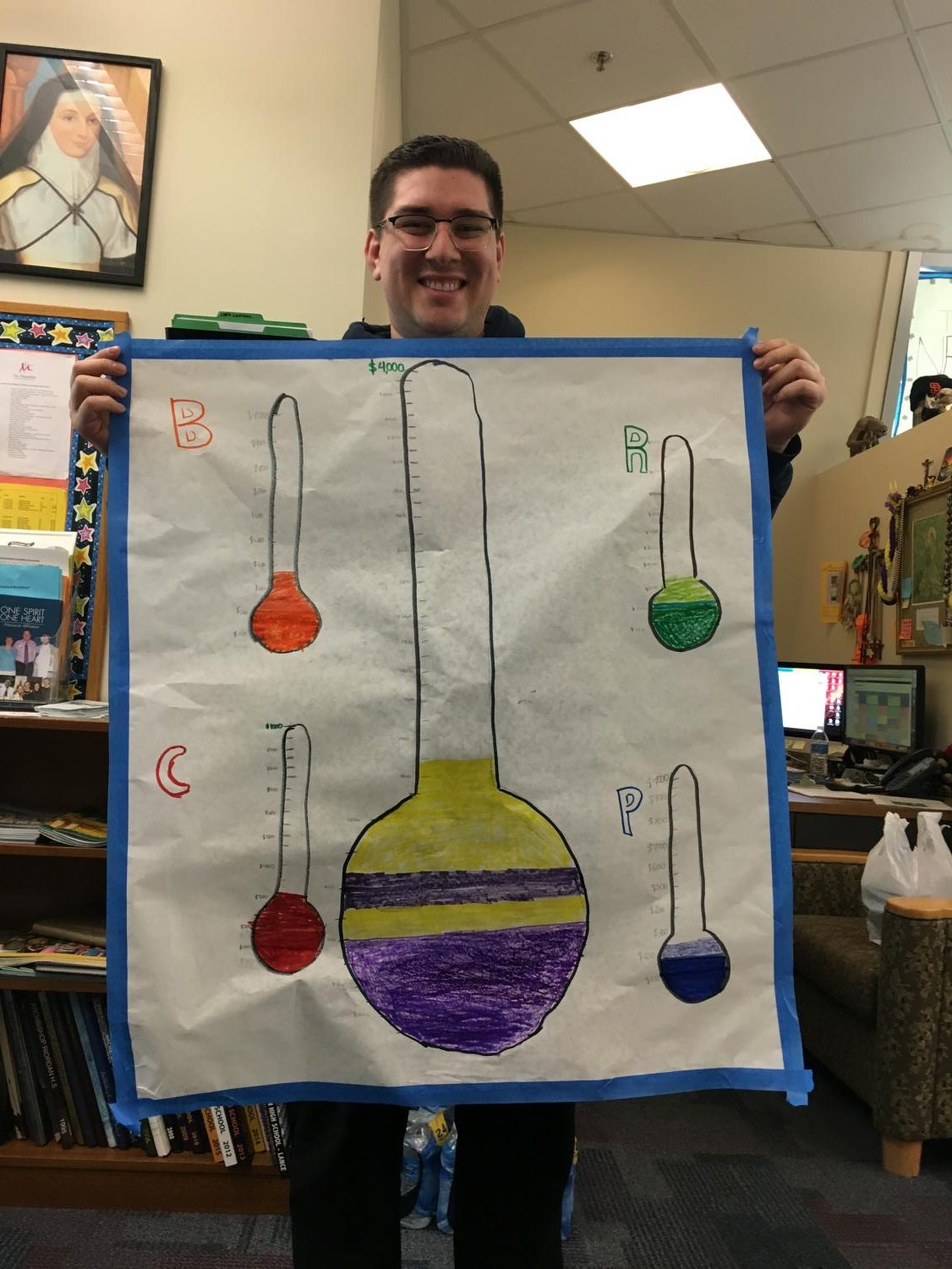 Leo Magnaye '05 holds a poster displaying the progress of the International Drive.