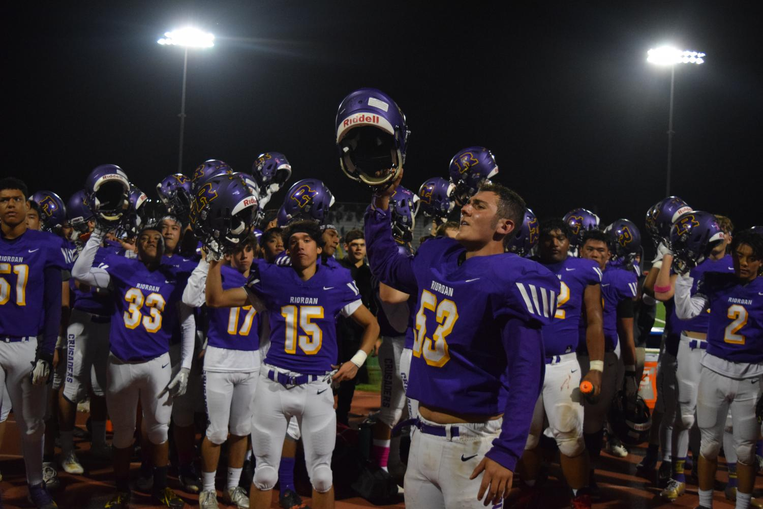 Members of the varsity football team sing the alma mater after a recent game.