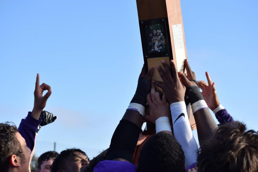 Members of the football team raise the Stanfel Trophy after winning