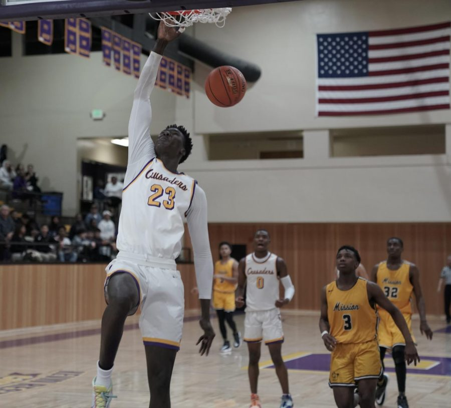 Varsity player Mor Seck '22 slam dunks against Mission High School.