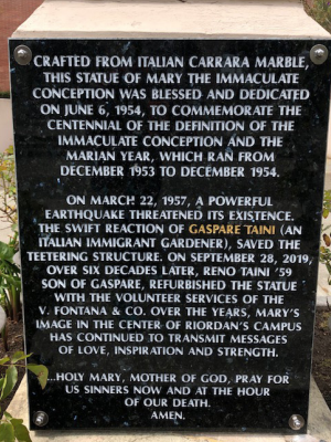 A plaque commemorates the dedication of the Mary statue in the courtyard and the gardener who saved it during an earthquake in 1957.