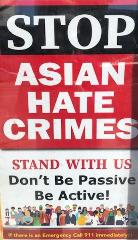 A sign in the window of a business on Ocean Avenue encourages people to stand together against hate crimes.