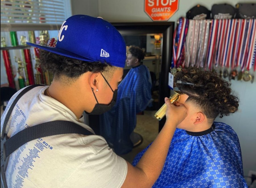 Barber Jacob Gregorio '22 styles the hair of Kevin Carranceja '21.