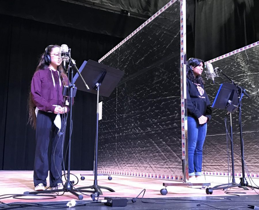 Marynna Mangibuyat 23 and Andrea Abraham 24 perform with partitions while Bella Mason 21 poses in front of a green screen for the musical We Will Rock You, featuring the music of Queen.
