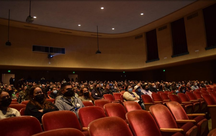 Parents watched a presentation about Riordan in the theatre with several speakers.