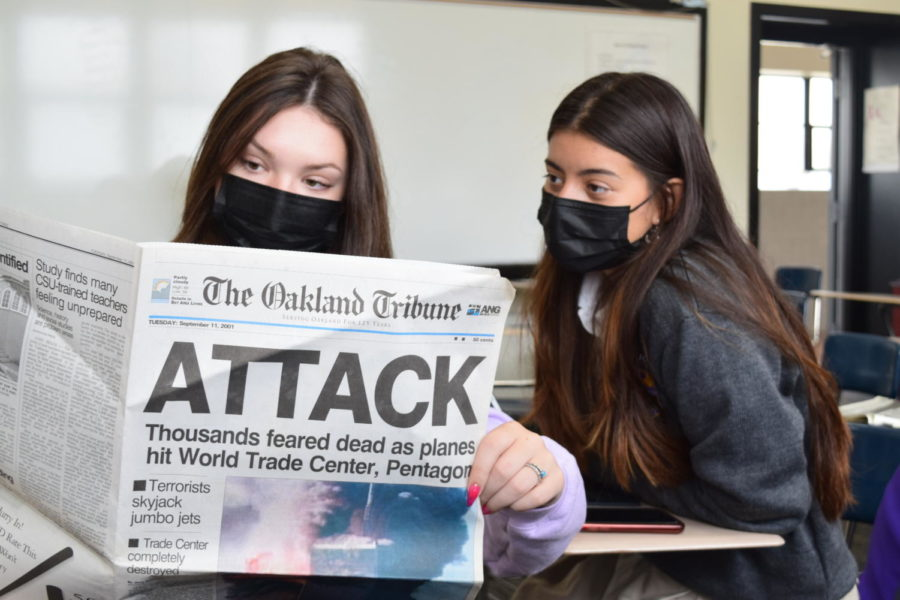 Delaney Mulqueen 22 and Sophia Carrasquilla 22, editors of The Crusader, read the front page section of a newspaper the day after 9/11 for a lesson in journalism class.